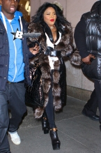 Rapper Lil Kim was in NYC to promote her comeback album. She stopped by MTV Studios wearing a big fur coat, bright red lipstick, and batty eyelashes.