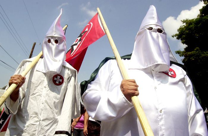 Members of the Ku Klux Klan march, Saturday, Aug. 28, 2004, through the streets of Sharpsburg, Md. A group of nine participants gathered at a community park near Antietam National Battlefield. They were outnumbered by more than two dozen police in riot gear who kept the Klansmen away from scores of people gathered in a downtown intersection. (