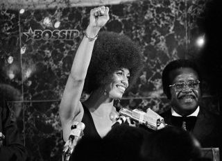 Angela Davis raises her fist in a Black Power salute after being introduced by Rev. Ralph Abernathy, president of the Southern Christian Leadership Conference, in Dallas, Texas, Aug. 17, 1972. Ms. Davis was the guest speaker at the 15th annual convention banquet; she spoke on revolutionary changes which included abolishing the prison system. (AP Photo/Charles Bennett)