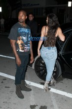Kim Kardashian Kanye West Prime One Twelve dinner in Miami SplashNews black lacy corset top wardrobe malfunction tupac gang related tee shirt