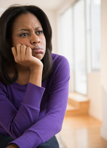 Anxious African American woman frowning