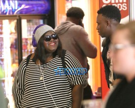 """Precious"" star, Gabby Sidibe smiles chats unidentified male friend arrival in Los Angeles. Oscar Nominated actress at LAX waiting for her luggage wearing her purple ""Beats by Dre"" headphones. SplashNews"