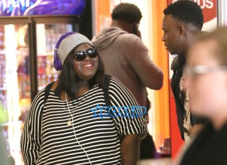 """""""Precious"""" star, Gabby Sidibe smiles chats unidentified male friend arrival in Los Angeles. Oscar Nominated actress at LAX waiting for her luggage wearing her purple """"Beats by Dre"""" headphones. SplashNews"""