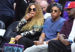 Beyonce snacks on potato chips as Jay Z watches Game 7 of the of the first round of the NBA Western Conference playoffs at the Staples Center Sunday. (Photo by Wally Skalij/Los Angeles Times via Getty Images)