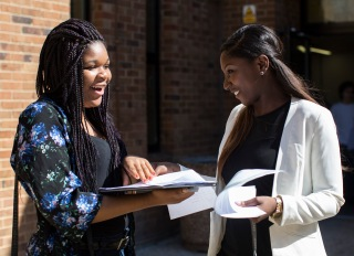 LONDON, ENGLAND - AUGUST 21: Girls react while opening their GCSE results at Stoke Newington school on August 21, 2014 in London, England. As hundreds of thousands of students opened their GCSE results today it has emerged that the proportion of GCSEs awarded A - C grade has risen to the highest in three years.