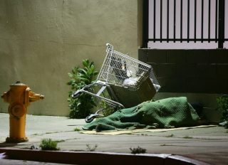 LOS ANGELES, CA - APRIL 19: A homeless person sleeps by his shopping cart on a downtown sidewalk in the early morning hours of April 19, 2006 in Los Angeles, California. Most homeless tents and improvised shelters are taken down at dawn, before their possessions can be hauled away by cleaning crews. A 9th U.S. Circuit Court of Appeals panel ruled last week that a city law making it illegal to sleep or sit on city sidewalks cannot be implemented as long as there is a shortage of homeless shelter beds in Los Angeles. According to a study released in January by the Los Angeles Housing Services Authority, there are nearly 90,000 homeless people live in Los Angeles County but only 9,000 to 10,000 beds available in homeless shelters, single-room occupancy hotels, and other facilities