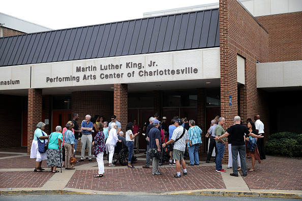 """CHARLOTTESVILLE, VA - AUGUST 27:  Residents arrive for a 'community recovery' town hall meeting conducted by the Department of Justice's Community Relations Service at the Dr. Martin Luther King Jr. Performing Arts Center at Charlottesville High School August 27, 2017 in Charlottesville, Virginia. The meeting follows an August 21 city council meeting that was overtaken by angry residents who screamed and cursed at councilors over the city's response to the """"Unite the Right"""" white supremacist rally. That August 12 rally devolved into street violence and left one counter-protester dead and two state trooper killed in a helicopter crash."""