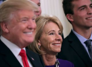 WASHINGTON, DC - NOVEMBER 17: (AFP OUT) U.S. President Donald Trump and Education Secretary Betsy Devos pose for photographs with members of the National Collegiate Athletic Association's champion University of Virginia men's tennis team in the East Room of the White House November 17, 2017 in Washington, DC. The White House welcomed athletes representing universities and colleges from across the country to meet Trump who congratulated them on their NCAA victories in sports like lacrosse, bowling, gymnastics, golf, rowing and others.