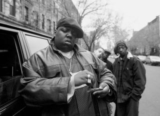 UNITED STATES - JANUARY 18: Rapper Notorious B.I.G., aka Biggie Smalls, aka Chris Wallace rolls a cigar outside his mother's house in Brooklyn.