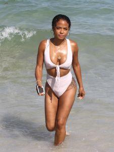 Christina Milian at the beach in Miami Beach, FL wearing a white tie up bikini by Myra Swim.