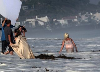 Lady Gaga topless wearing a bikini and thong lingerie for a photoshoot on the beach in Malibu California. The wet and wild photographers and crew got soaked by the big waves.