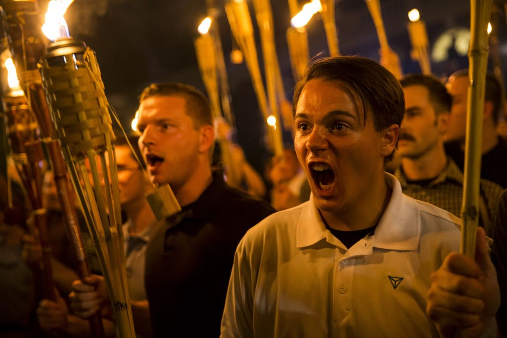 CHARLOTTESVILLE, USA - AUGUST 11: Peter Cvjetanovic (R) along with Neo Nazis, Alt-Right, and White Supremacists encircle and chant at counter protestors at the base of a statue of Thomas Jefferson after marching through the University of Virginia campus with torches in Charlottesville, Va., USA on August 11, 2017.
