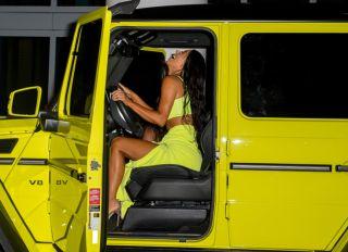 Kim Kardashian revealing neon outfit Miami Beach. reality TV diva wore a fluorescent yellow ensemble in the same eye catching shade as her Mercedes G Wagon.