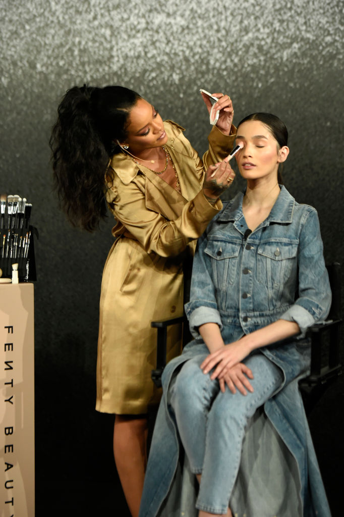"""DUBAI, UNITED ARAB EMIRATES - SEPTEMBER 29: Rihanna applies make up on a model during her Fenty Beauty talk in collaboration with Sephora, for the launch of her new Stunna Lip paint """"Uninvited"""" on September 29, 2018 in Dubai, United Arab Emirates."""