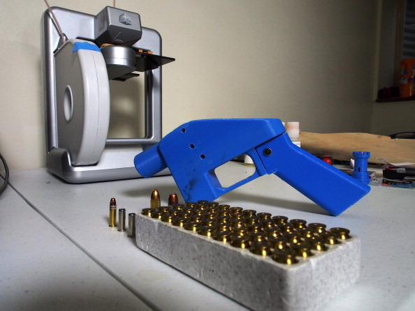 TO GO WITH AFP STORY BY ROBERT MACPHERSON A Liberator pistol appears on July 11, 2013 next to the 3D printer on which its components were made. The single-shot handgun is the first firearm that can be made entirely with plastic components forged with a 3D printer and computer-aided design (CAD) files downloaded from the Internet.