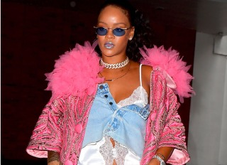 Rihanna has been out of the spotlight for months, enjoying some off time in London, but she is back and she is looking better than ever. She stunned in a double denim look as she headed to an office building in NYC while preparing for the Met Gala. She showcases a piece from her upcoming Savage x Fenty Lingerie line , a white lace night shirt, under what appeared to be a Denim skirt worn as a top. She topped it off with a pink coat.