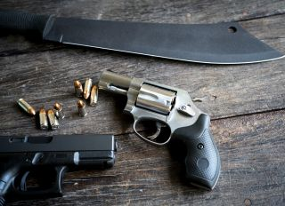 High Angle View Of Handgun And Pistol With Knife On Table