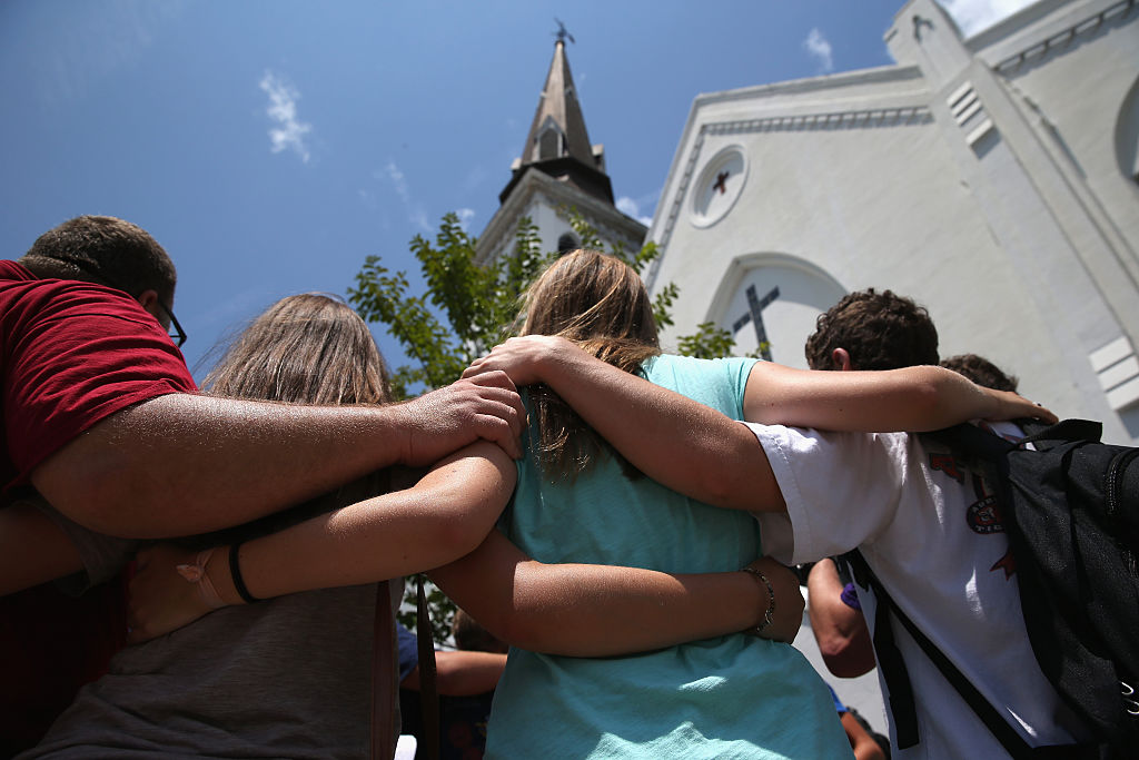 """CHARLESTON, SC - JULY 17:  A church youth group from Douthan, Alabama prays in front of the Emanuel AME Church on the one-month anniversary of the mass shooting on July 17, 2015 in Charleston, South Carolina. Visitors from around the nation continue to pay their respects at a makeshift shrine in front of the church, in a show of faith and solidarity with """"Mother Emanuel"""", as the church is known in Charleston. Nine people were allegedly murdered on June 17 by 21-year-old white supremacist Dylann Roof, who was captured by police in North Carolina the following day. He is scheduled to go to trial July 11, 2016."""