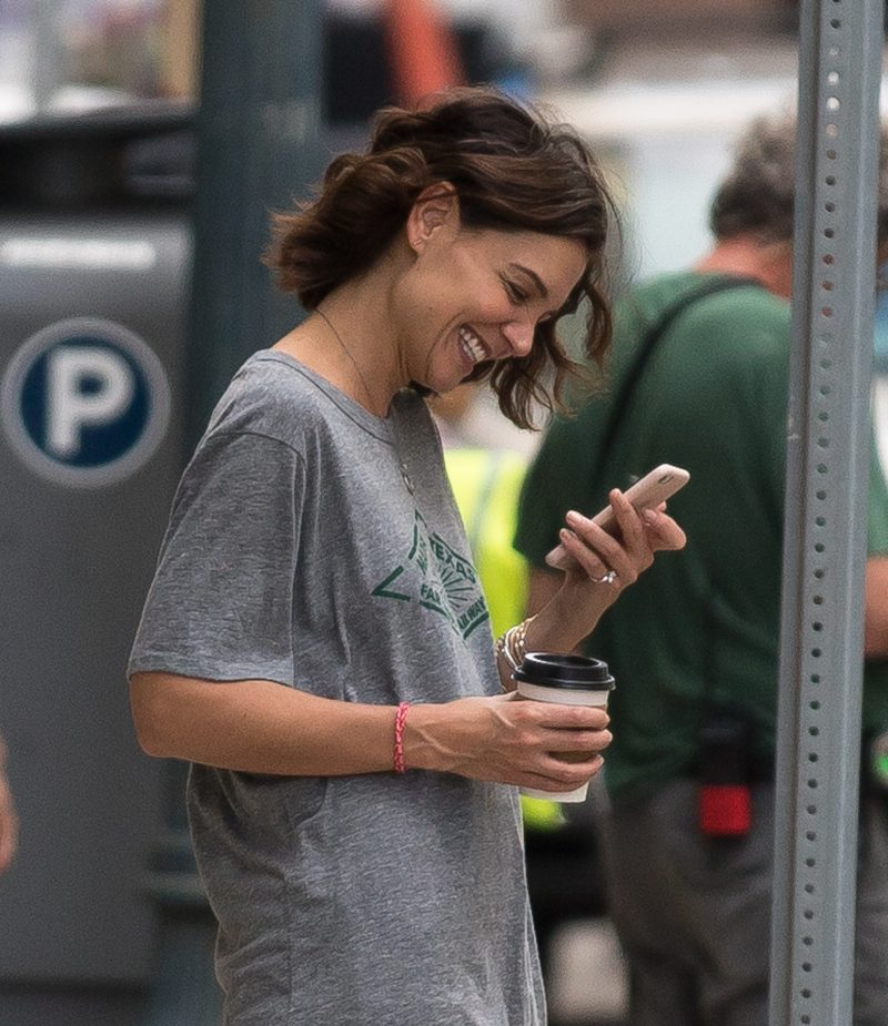 Katie Holmes looks happy while taking a break from filming in New Orleans on Wednesday. Katie was on the set of her new movie The Secret and was spotted wearing a diamond ring on her little finger as she chatted on FaceTime on her phone. Her boyfriend Jamie Foxx is also in town shooting a different movie.
