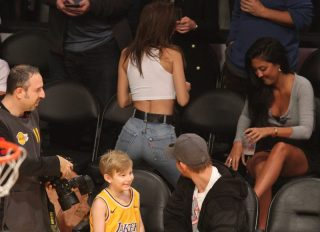 Model Emily Ratajkowski manages to get a dad who was sitting in front of her checking out her buns as she shows of her spectacular assets as she poses courtside while attending the Los Angeles Lakers Vs The Minnesota Timberwolves game at The Staples Center in Los Angeles, Ca