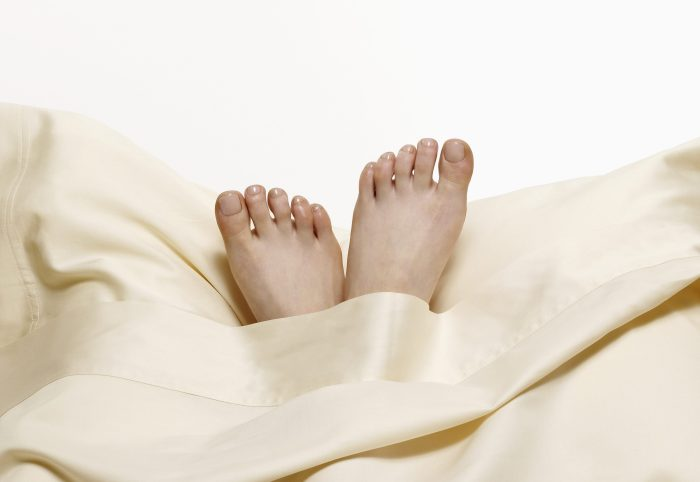 Woman?s feet on pillow in bed