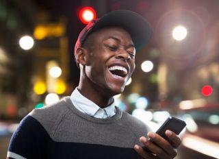 Man laughing at phone in urban street at night