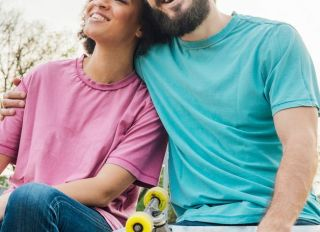 Smiling skater man hugging his girlfriend while sitting in the park