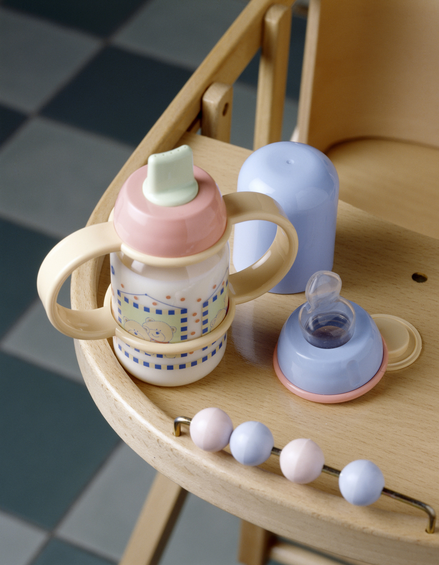 Baby bottle full of milk on a high chair