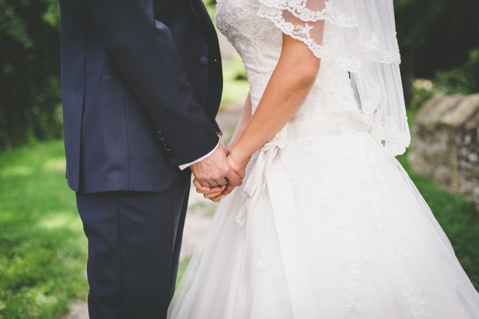 Midsection Of Couple Holding Hands At Wedding