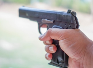 Cropped Image Of Hand Holding Gun