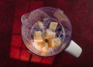 Blueberry smoothie ingredients in countertop blender