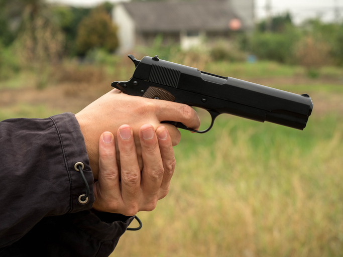 Cropped Hands Of Thief Holding Gun On Field