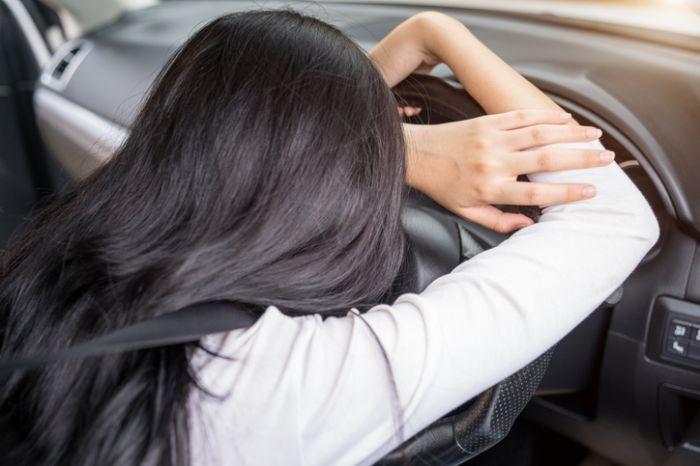woman sleepy driving in car