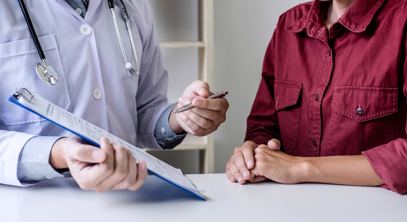 Midsection Of Doctor Showing Report To Patient On Table In Medical Clinic