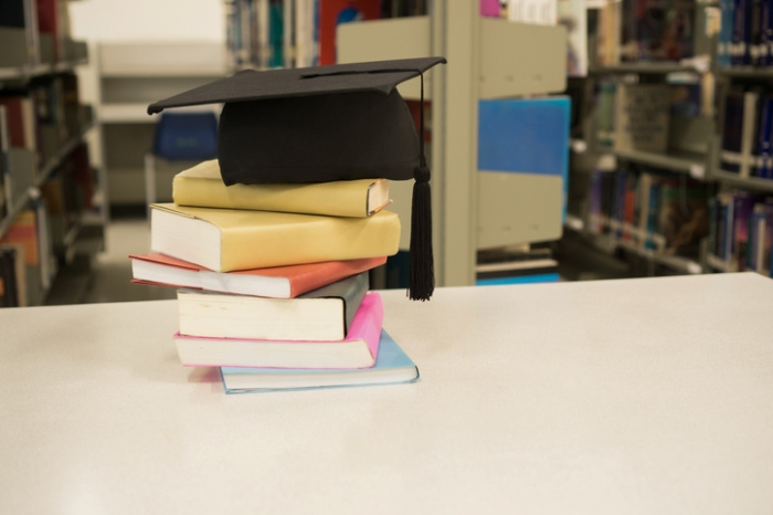 Stack Of Books And Mortarboard On Table
