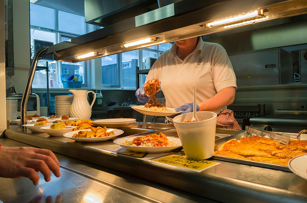 A woman serving food in a school canteen, Wales UK