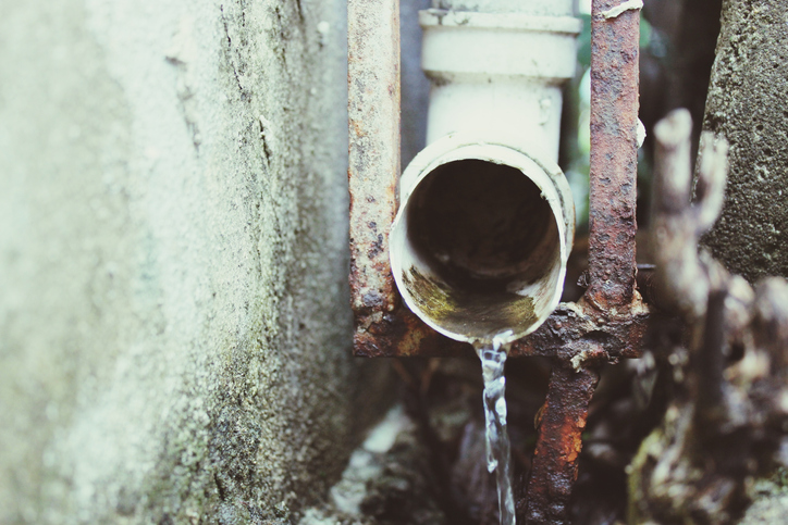Close-Up Of Water Falling From Rustic Pipe