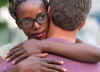 African woman embracing her boyfriend on the street