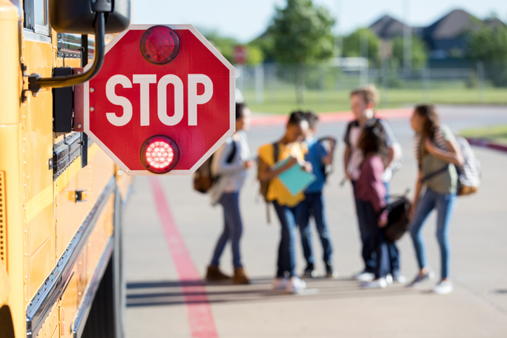 Group of school children talk outside bus