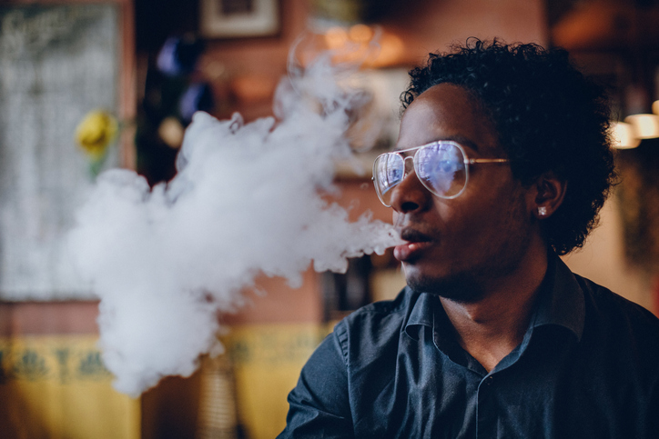 Young man smoking electronic cigarette in pub