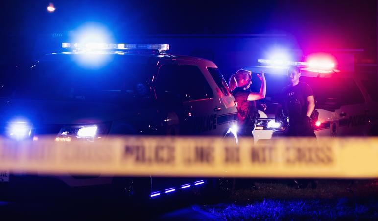 Police officers in bulletproof vests behind cordon tape