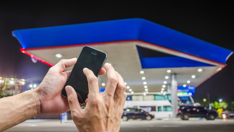 Cropped Hand Of Person Using Mobile Phone Against Gas Station At Night