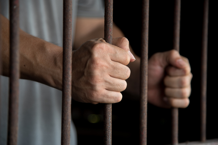 Close-Up Of Man Holding Prison Bars