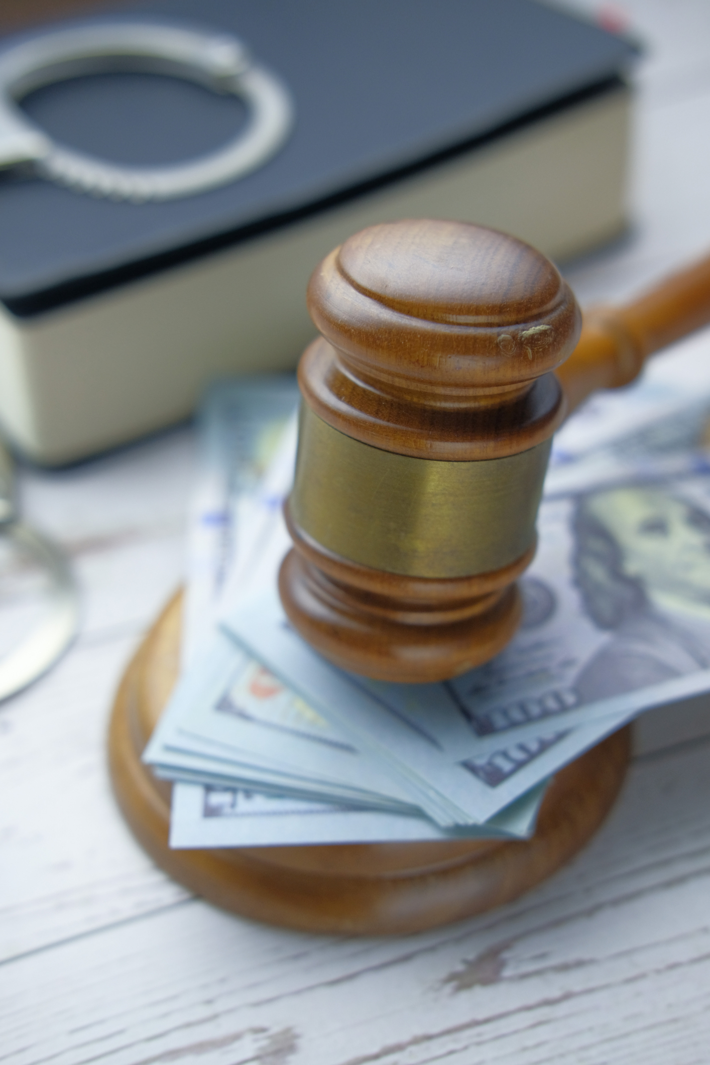 Gavel on cash with handcuff on table