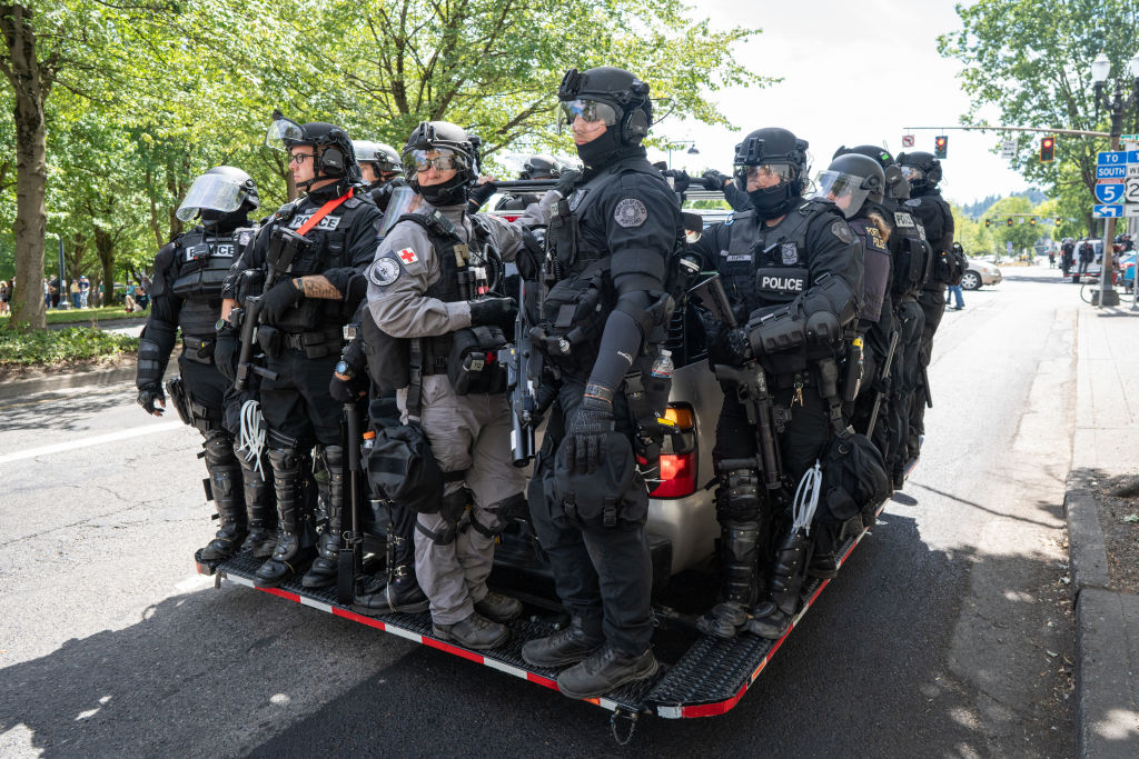 Police clad in riot gear wait to be called into action...