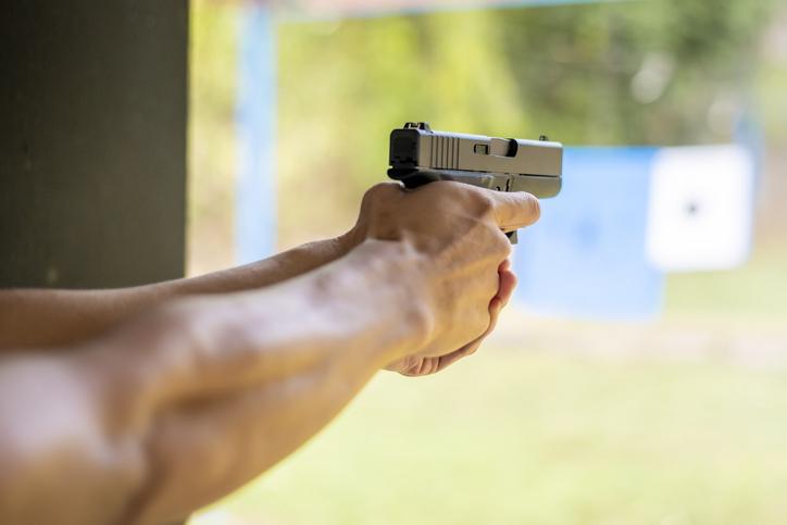 Cropped Hands Of Man Aiming Gun
