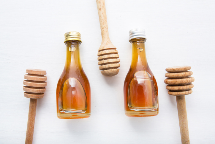 Directly Above Shot Of Honey In Bottles With Dippers Over White Background