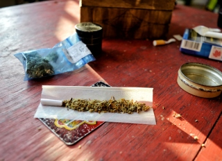High Angle View Of Marijuana Joint Being Prepared On Wooden Table