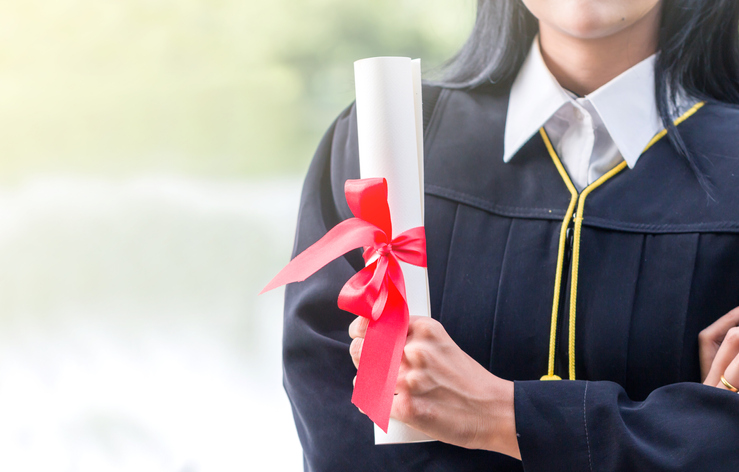 Midsection Of Woman In Graduation Gown Holding Certificate
