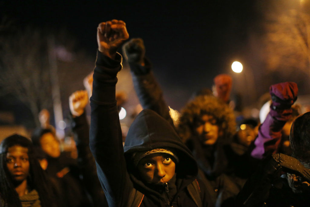 A young protester raised his fist during a moment of silence for Jamar Clark during a concert in front of the Fourth Precinct on Plymouth Avenue North Tuesday November 24 2015 in Minneapolis, MN.] Jerry Holt/ Jerry.Holt@Startribune.com